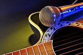 Acoustic guitar and microphone isolated with yellow and blue lig