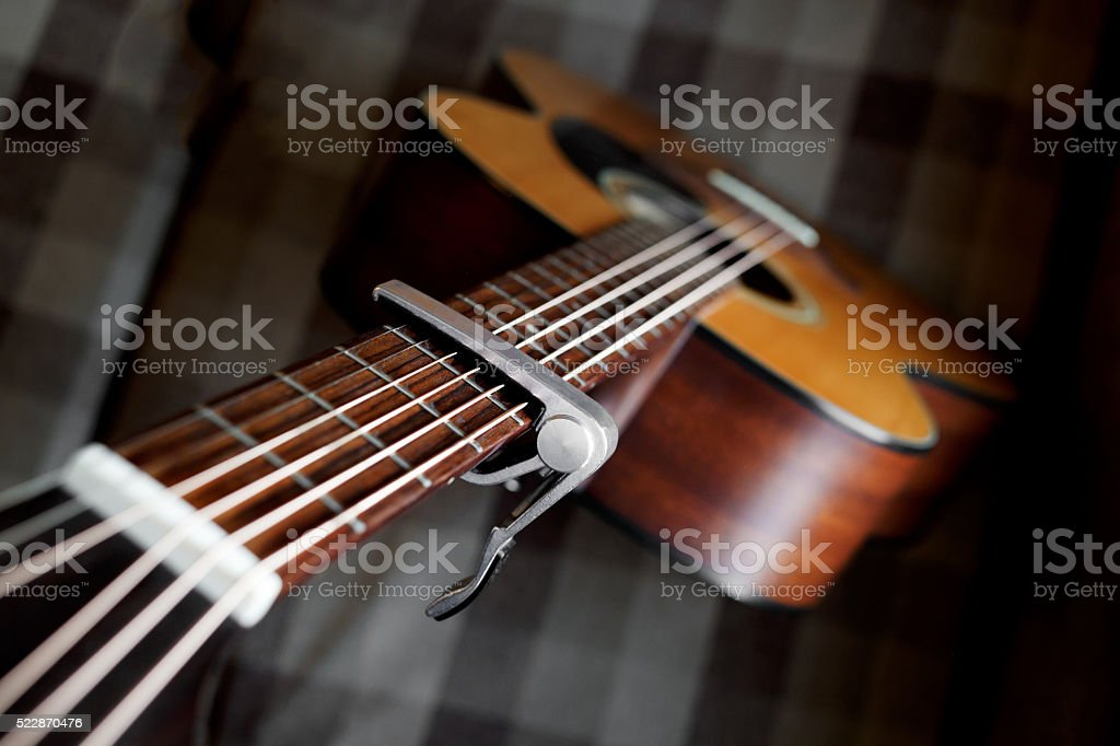 Acoustic guitar neck with a capo stock photo