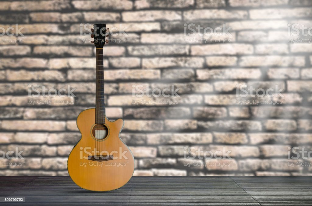 acoustic guitar on the wooden floor against  brick wall background. stock photo