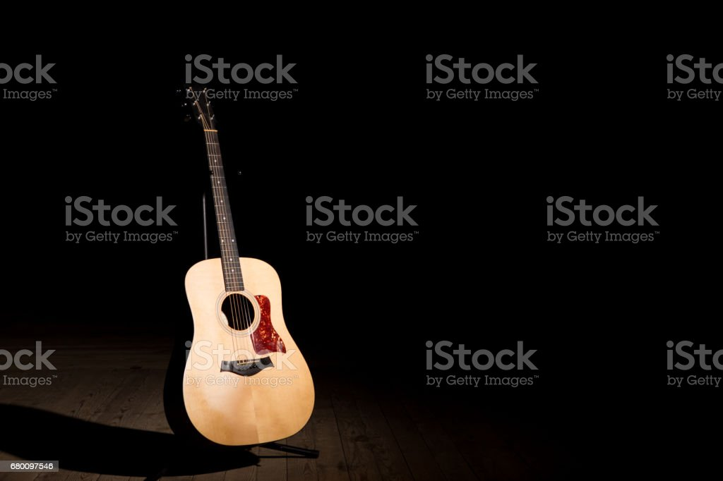 Acoustic guitar over dark background with copy space stock photo