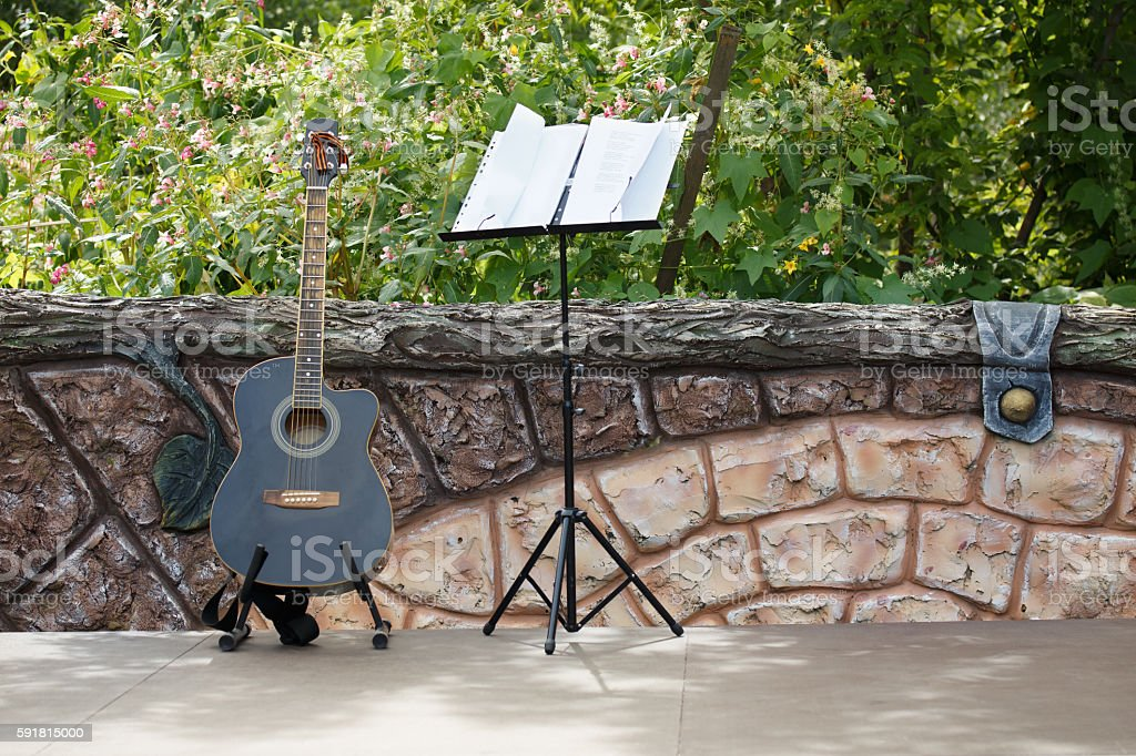 Acoustic guitar standing on the open stage near the fence stock photo