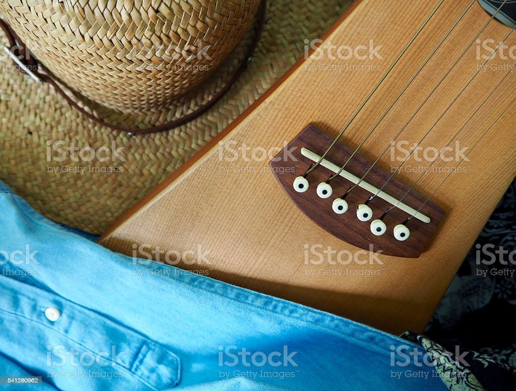 Acoustic guitar ,straw hat and blue jean shirt stock photo