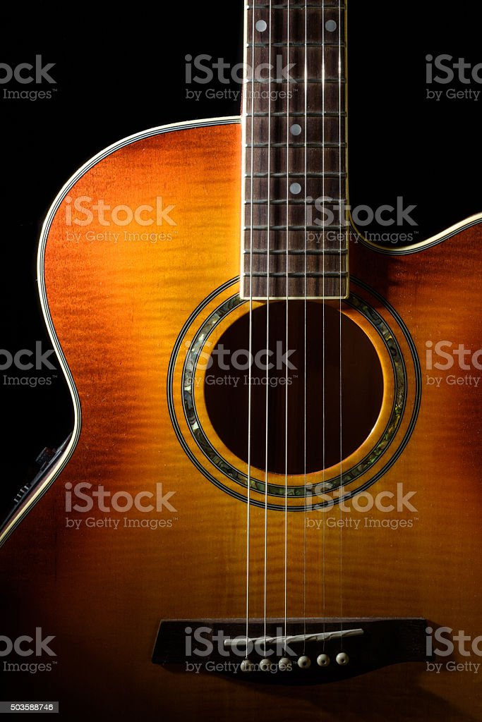 Acoustic guitar with a black background stock photo