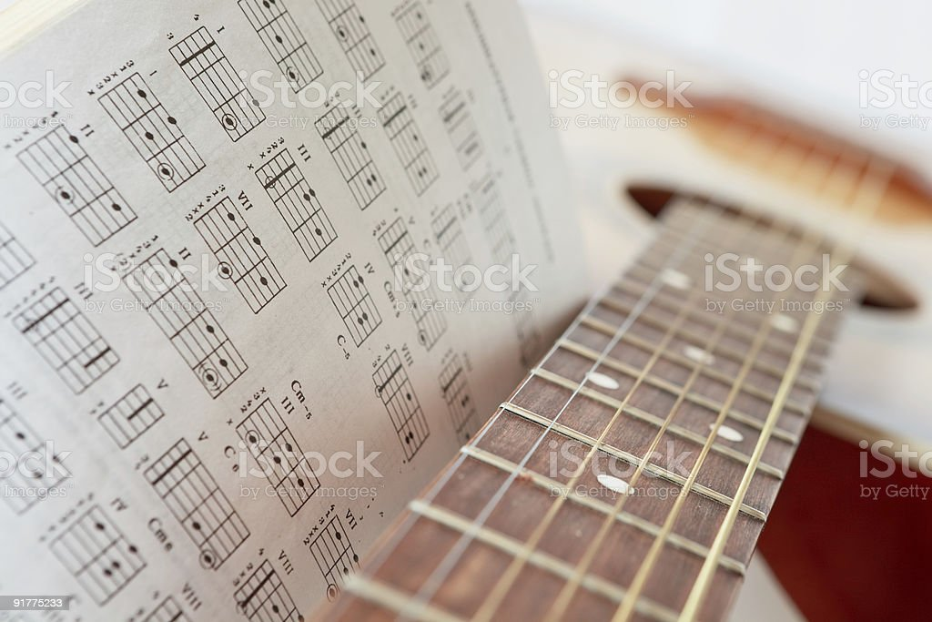 Acoustic guitar with a book of chords stock photo