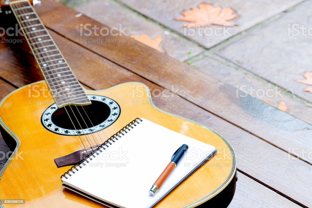 acoustic guitar with notebook and pen on wood background stock photo