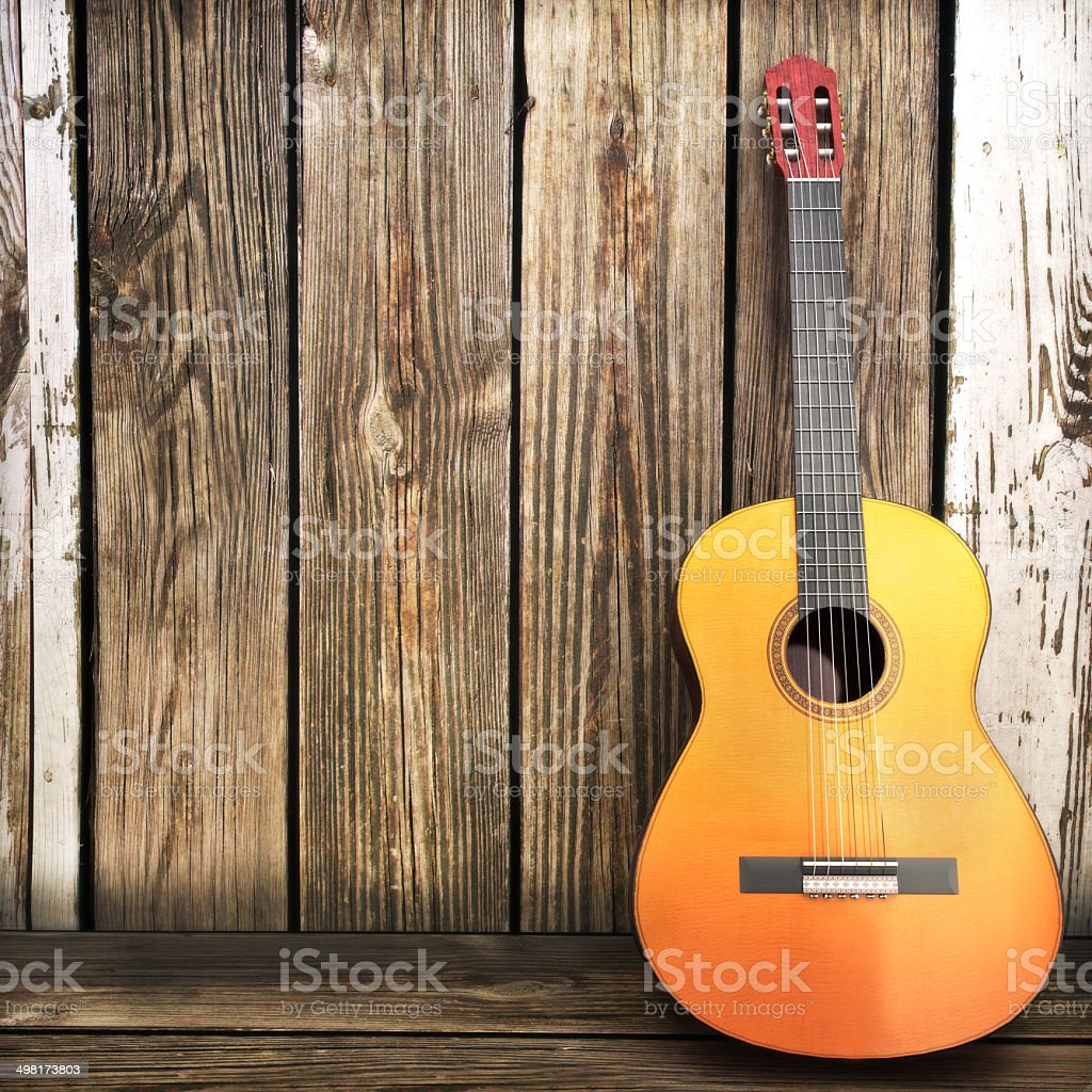 Acoustic wooden guitar leaning on a wooden fence. stock photo