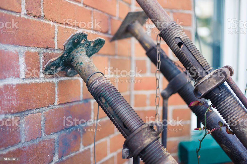 Acro supports leaning against brick wall stock photo