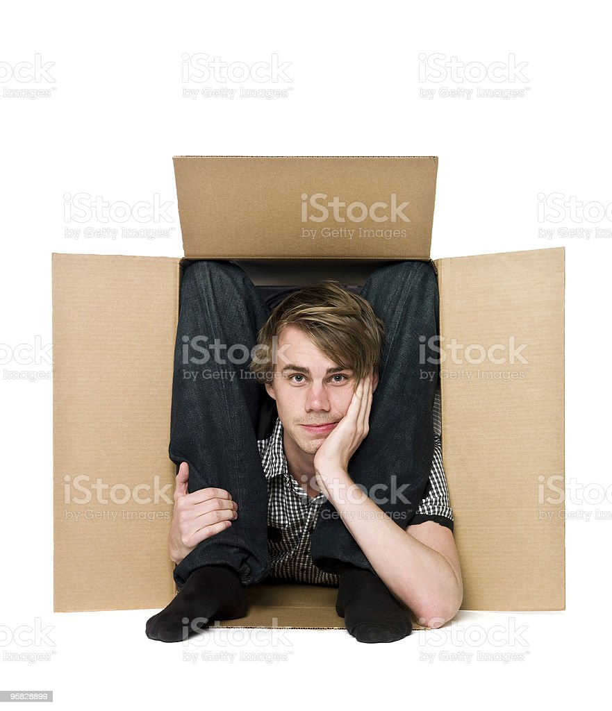 Acrobat inside of a cardboard box. stock photo