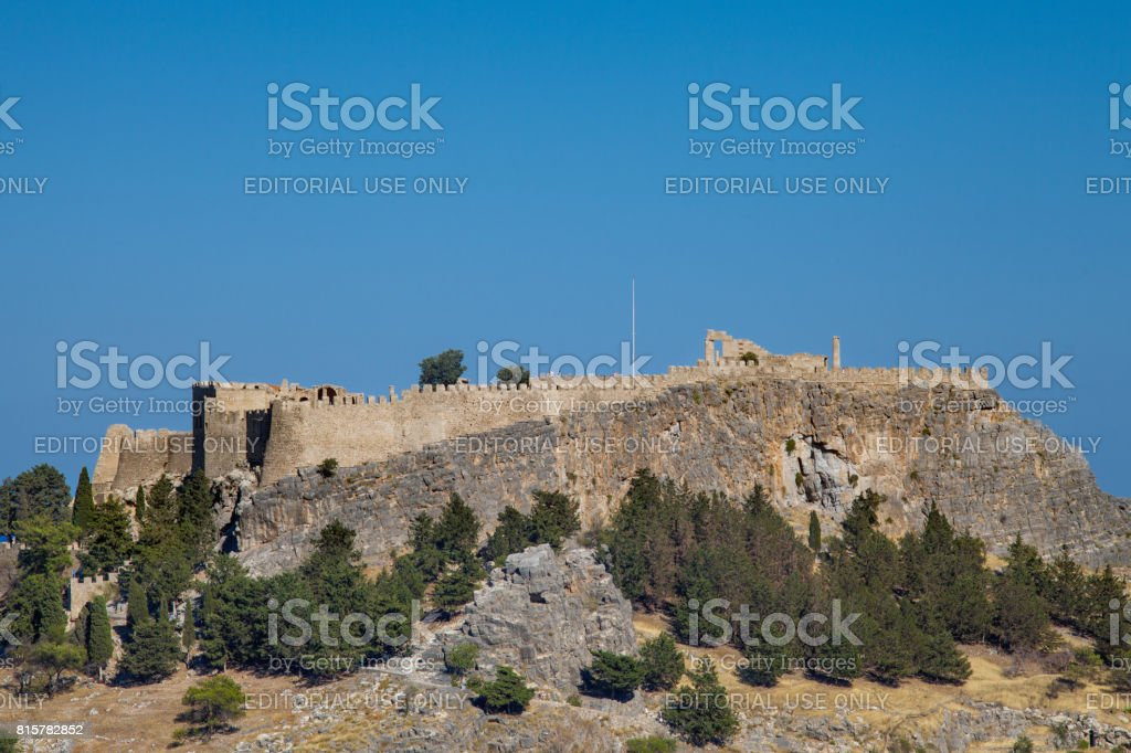 Acropolis on a hill in the city of Lindos. Fragment of residential buildings at the foot of the mountain. stock photo