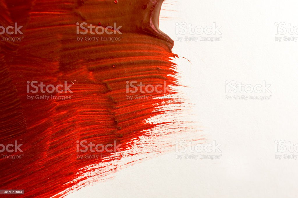Acrylic red paint with brush marks on white- copy space stock photo