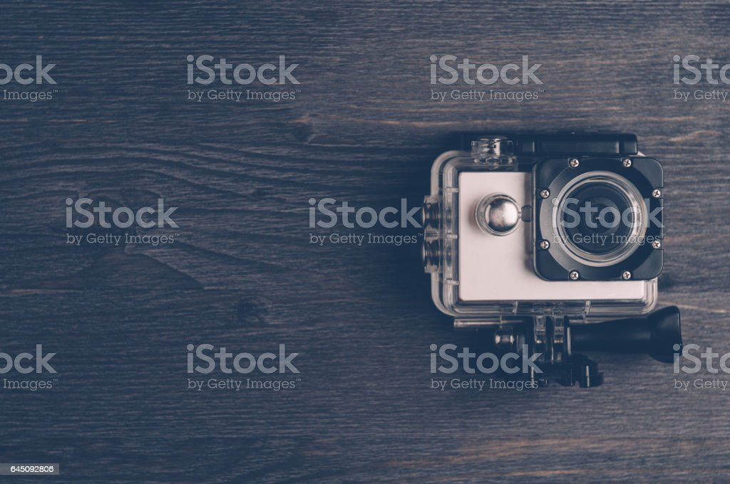 Action camera on a dark wooden background. Travel concept stock photo