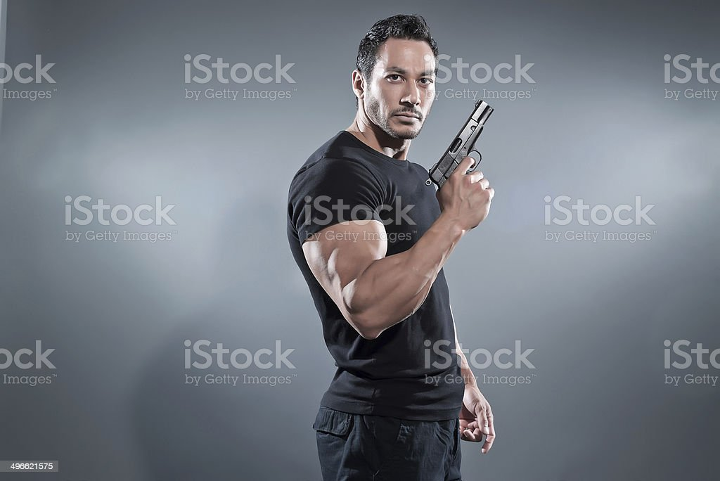 Action hero muscled man holding a gun. Wearing black t-shirt and...