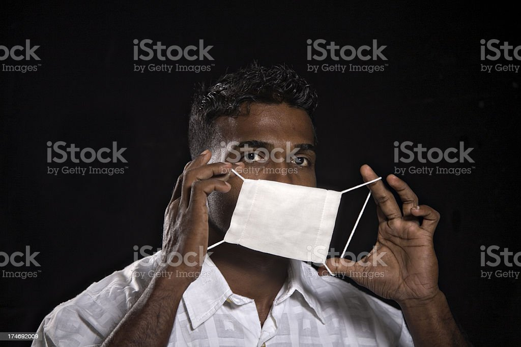 action of man putting on flu face mask stock photo