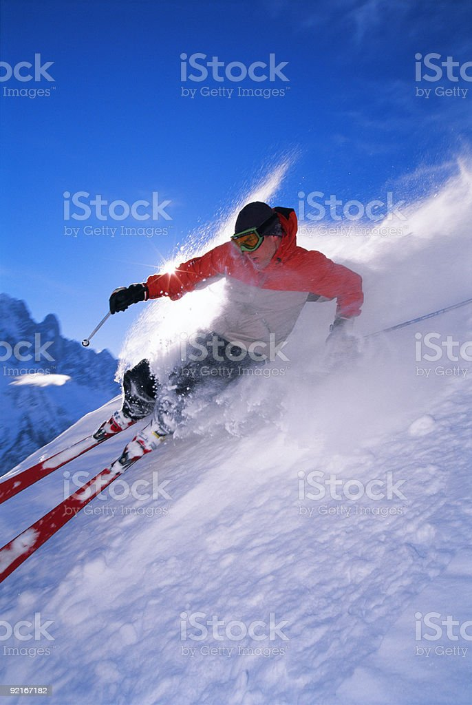 Action photo of man skiing down steep slope stock photo