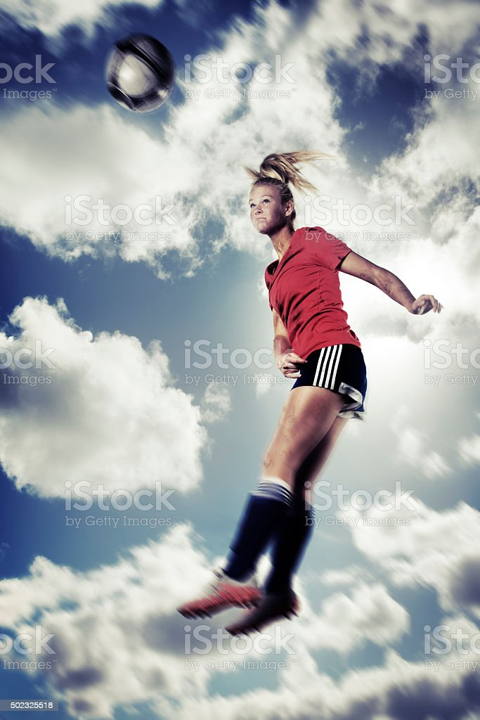 Action Portrait of Ball Headed by Female Teenage Soccer Player stock photo