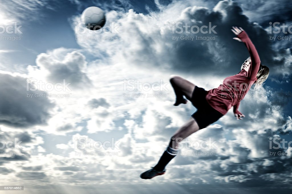 Action Portrait of Ball Kicked by Female Teenage Soccer Player stock photo
