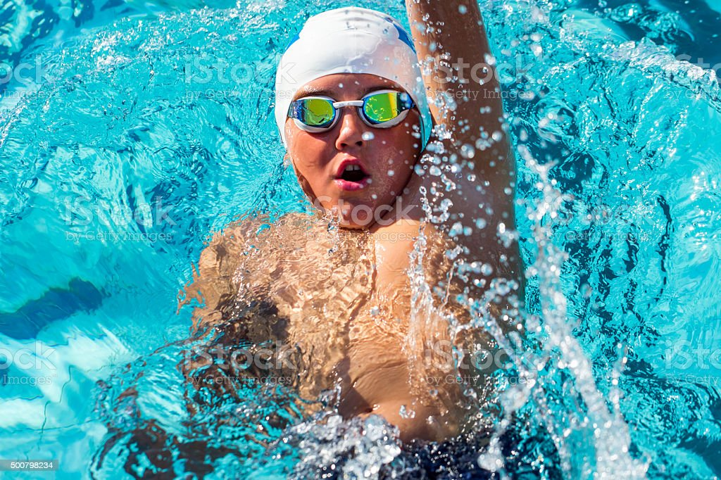 Action shot from top of boy swimming backstroke. stock photo