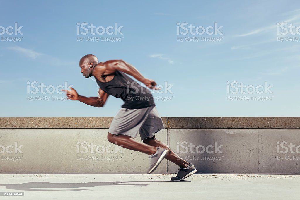 Action shot of a sporty young man running outdoors stock photo