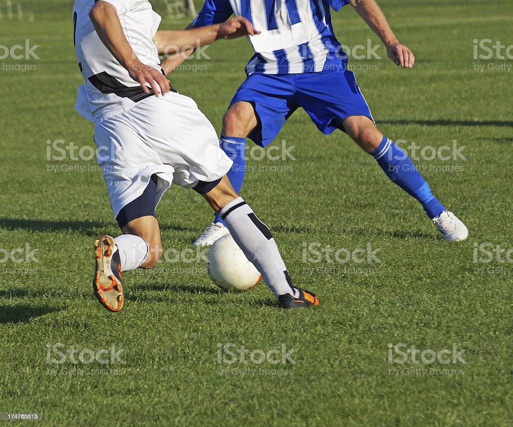 Action shot of two opposing soccer players royalty-free stock photo