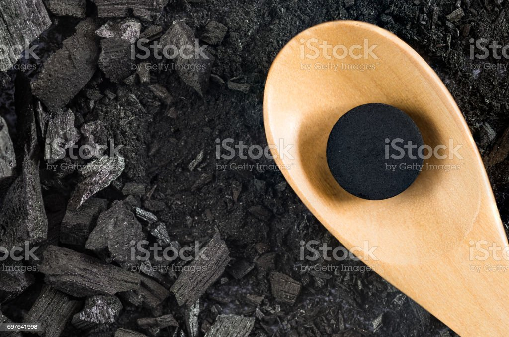 activated carbon pill medicine in wooden spoon on ground charcoal texture background, top view stock photo