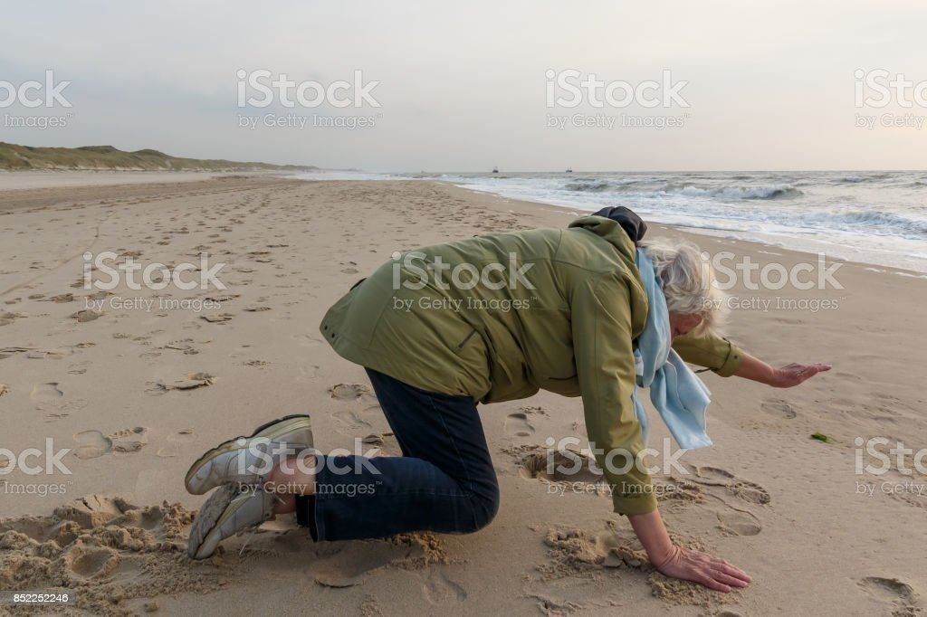 Active 72 years old  female senior excersicing on the beach. stock photo