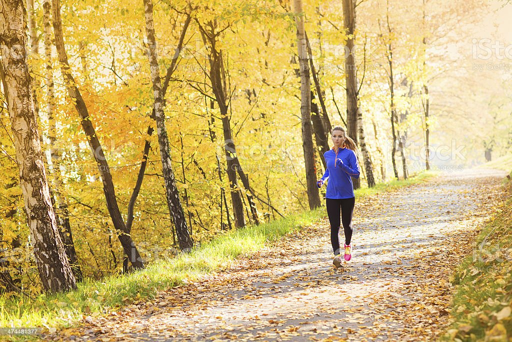 Active and sporty woman runner in autumn nature stock photo