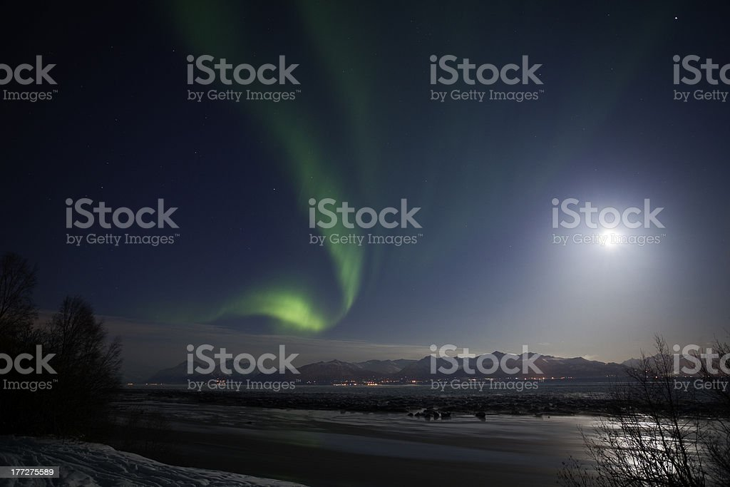Active Aurora shines through Full Moon Light stock photo