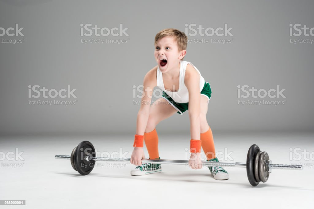 active boy in sportswear training with barbell isolated on grey stock photo