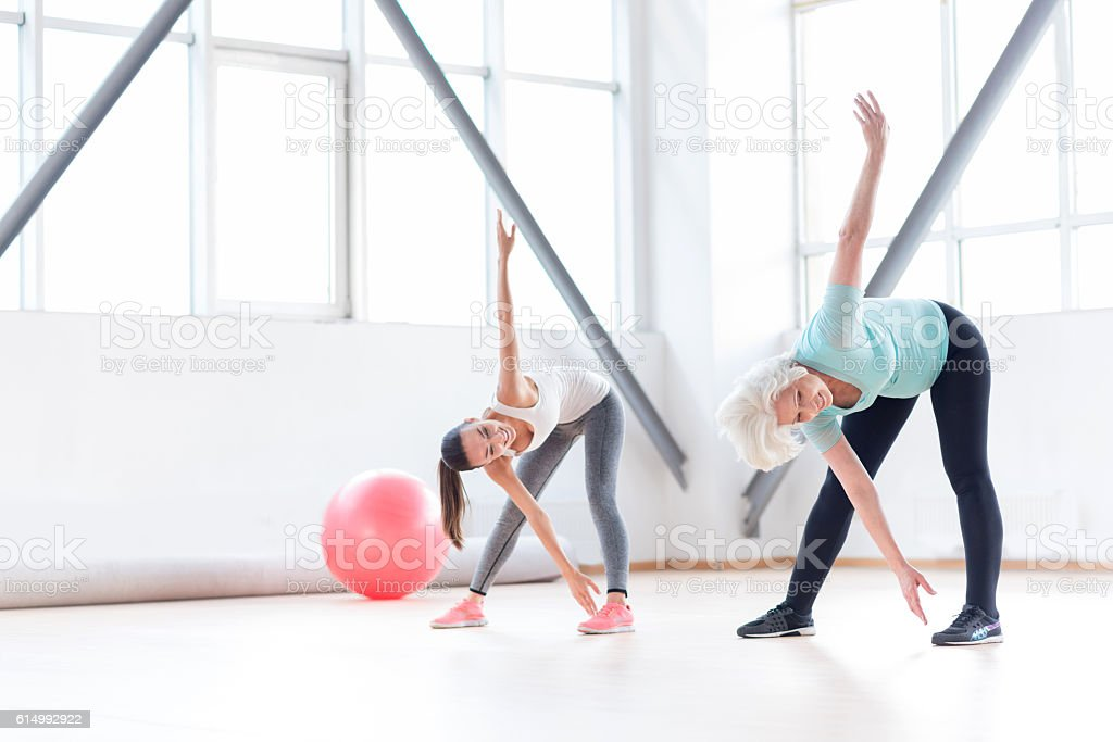 Active cheerful women exercising in a fitness club stock photo