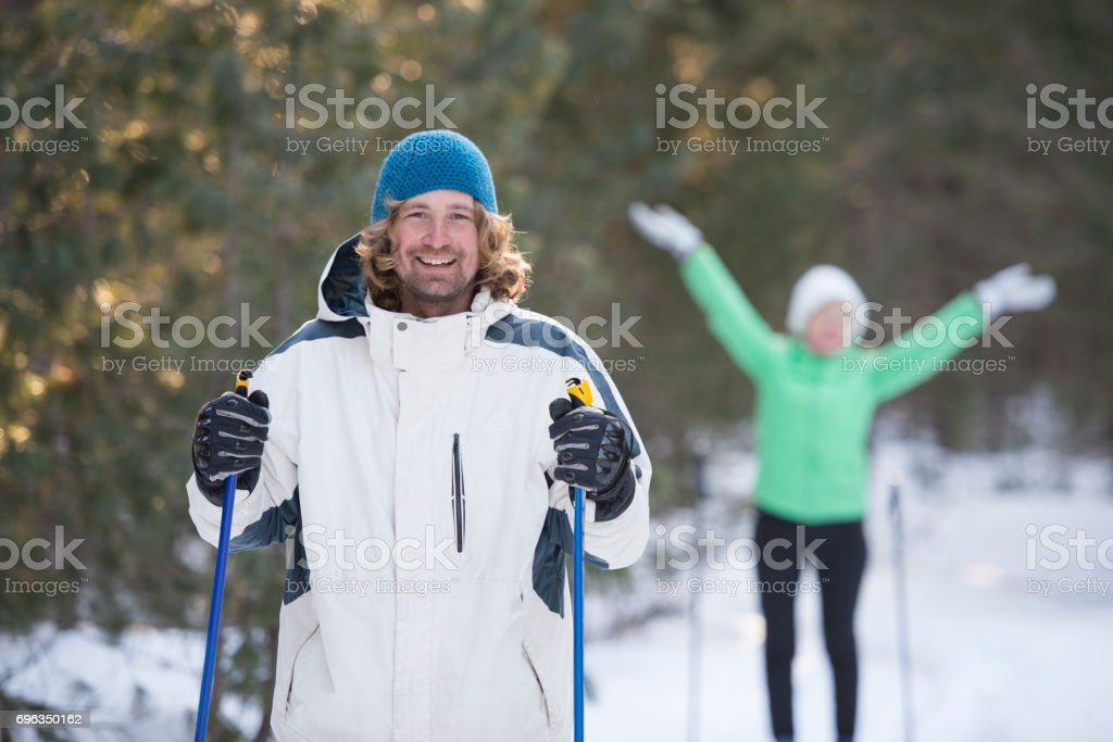 Active couple cross-country skiing in the Taiga forest, Siberia....