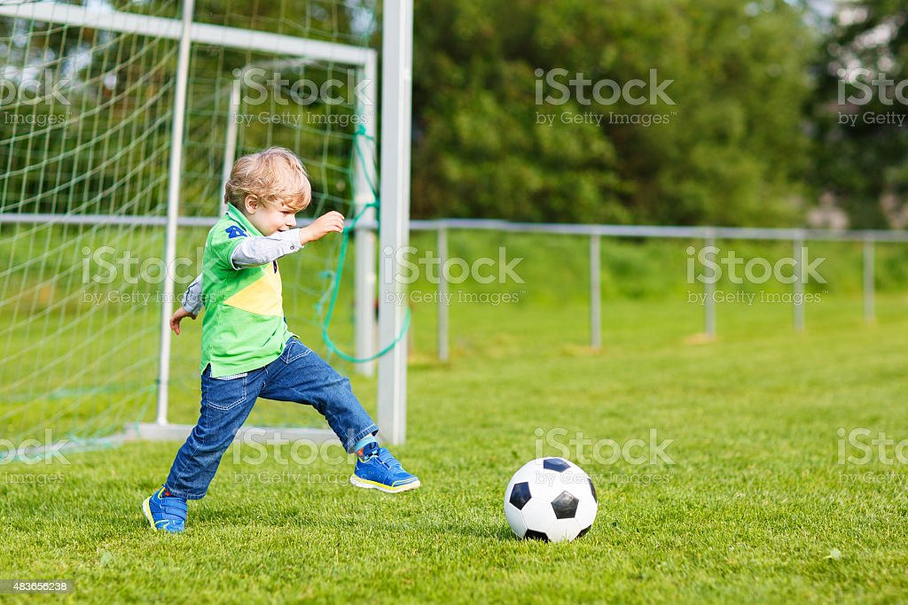 Active cute little kid boy playing soccer and football stock photo