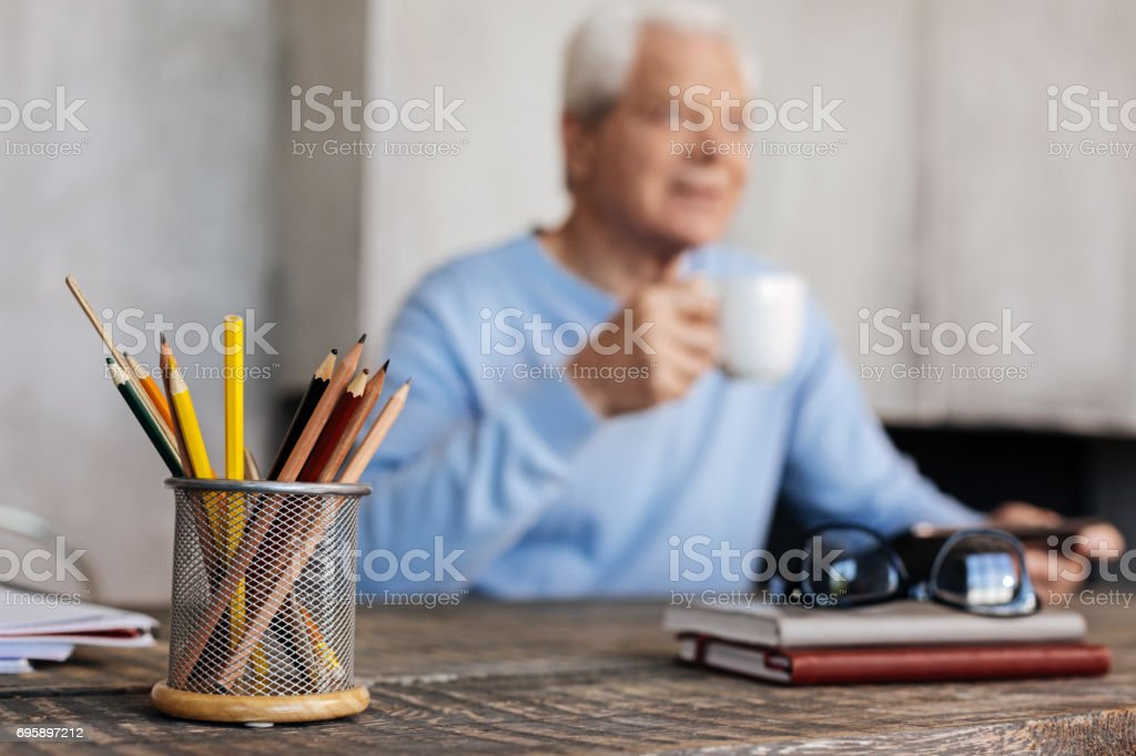 Active elderly man sitting at the table at home office stock photo