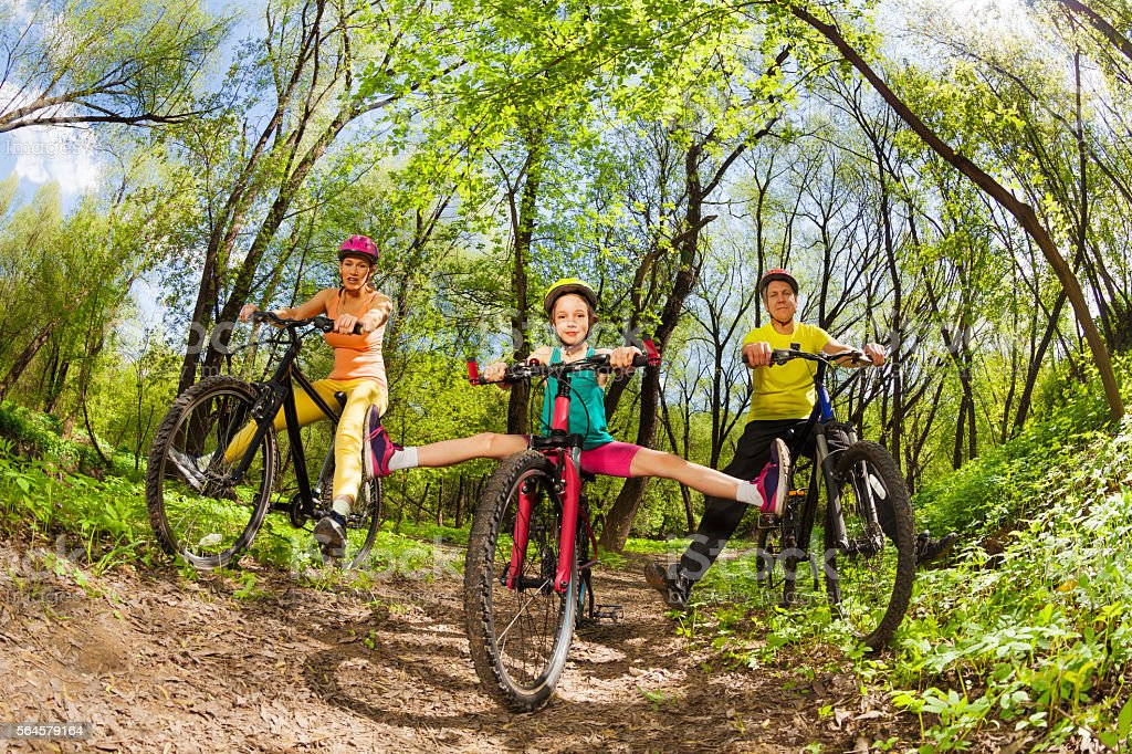 Active family cycling down the woods trail stock photo