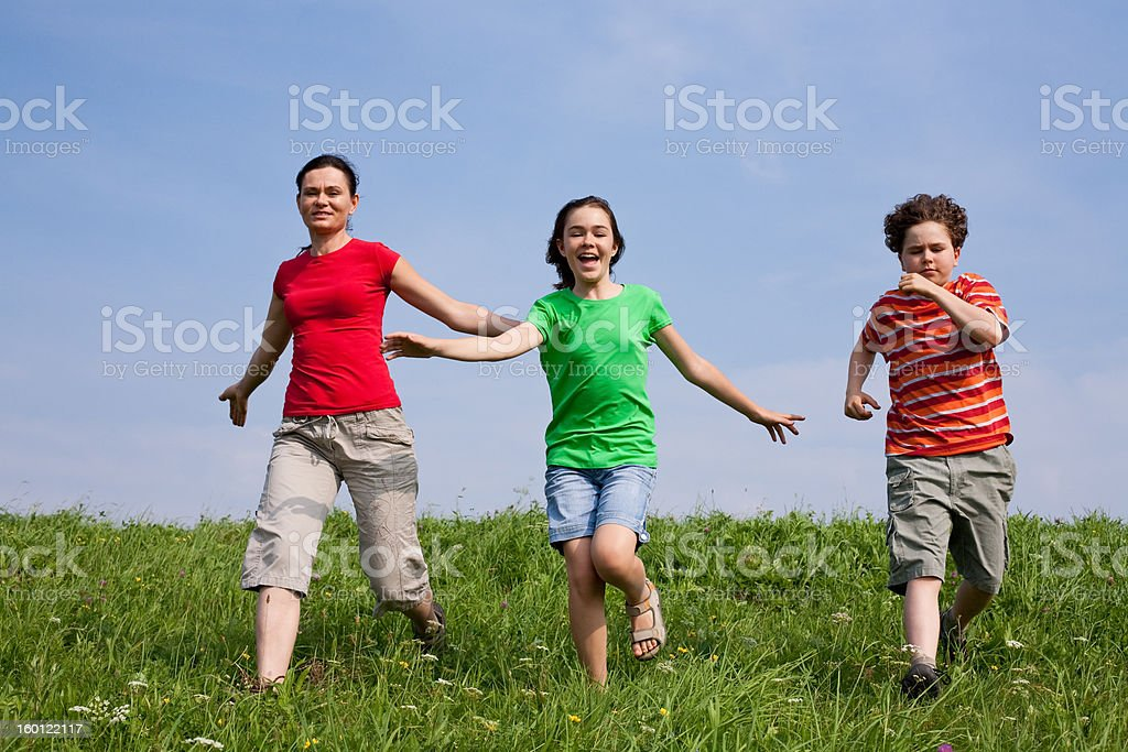 Active family running on green meadow royalty-free stock photo