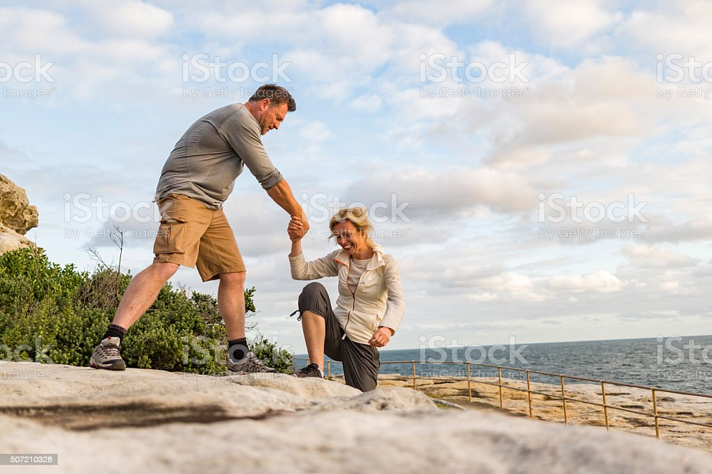 Active Fit Mature Couple Helping Each Other Hiking stock photo