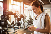Active girl using smartphone in fitness gym.