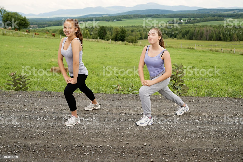 Active girls exercising and stretching in nature. royalty-free stock photo