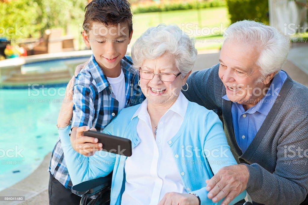 Active grandparents enjoy taking selfie with grandson stock photo