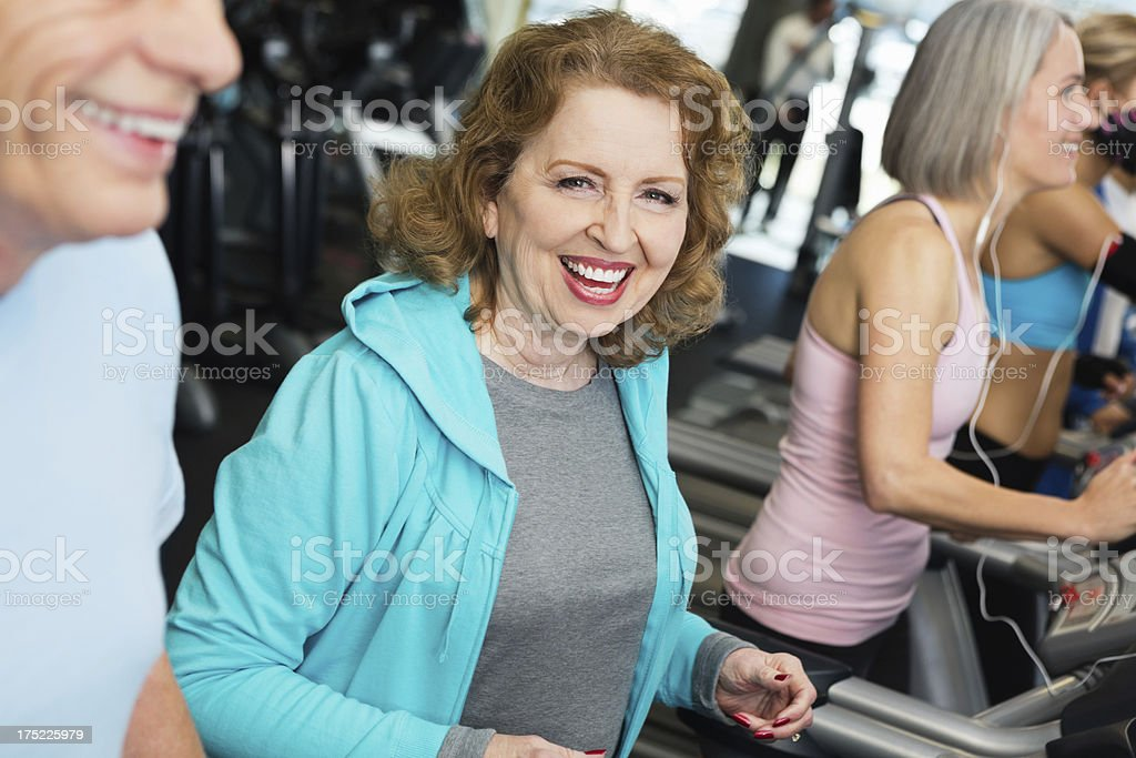 Active group of seniors jogging on treadmills in gym royalty-free stock photo