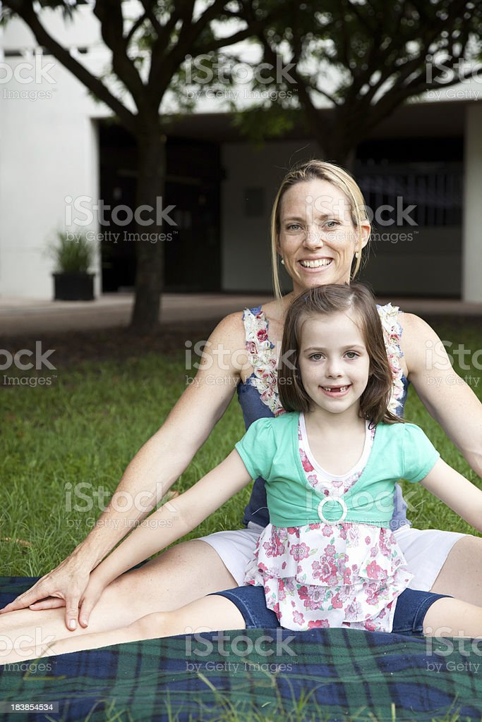 Active healthy mother and daughter outdoors sitting in splits pose royalty-free stock photo