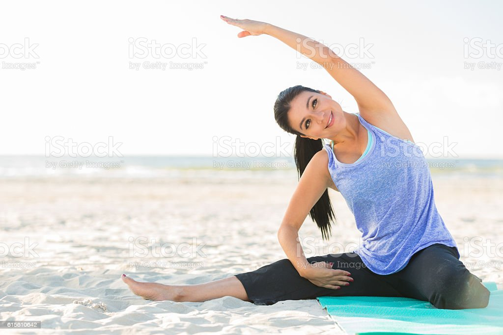 Active Hispanic woman does yoga at the beach stock photo