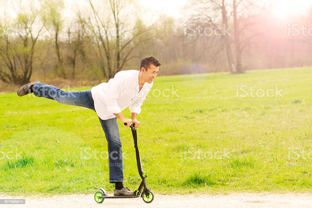 Active Japanese man having fun while riding a push scooter stock photo