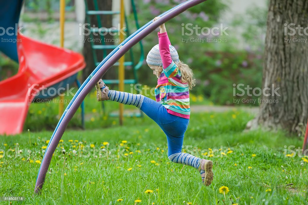 Active little girl climbing monkey bar outdoors on spring playground stock photo