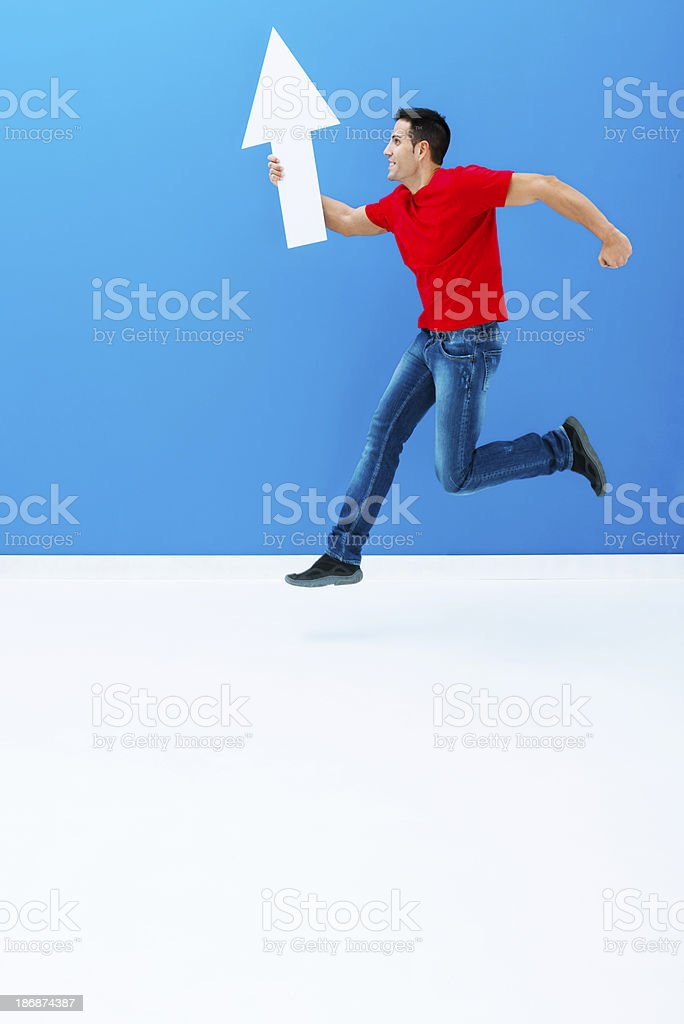 Active man pointing up with arrow stock photo