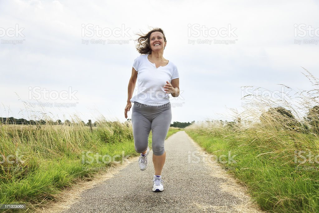 active mature woman jogging outdoors stock photo