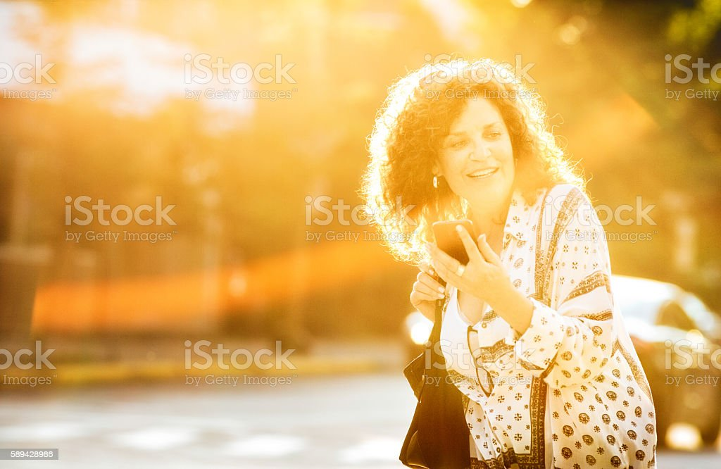 Active mature woman waiting for car pool or bus stock photo