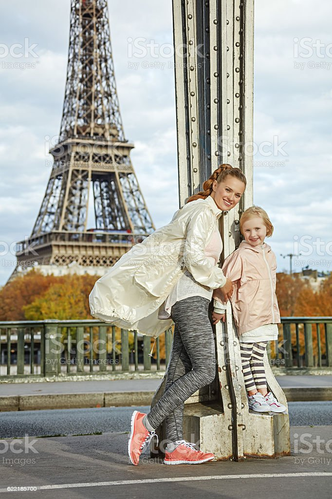 active mother and child standing on Pont de Bir-Hakeim bridge stock photo
