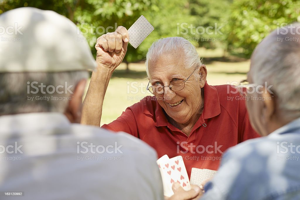 Active retired people, three senior men playing chess at park stock photo