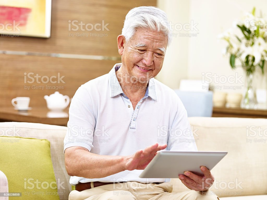 active senior asian man using tablet computer stock photo
