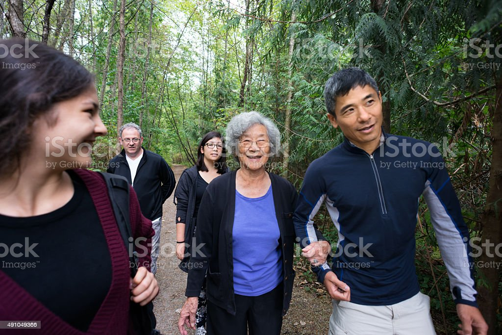 Active Senior Asian Woman Walking in Wooded Trail with Family stock photo